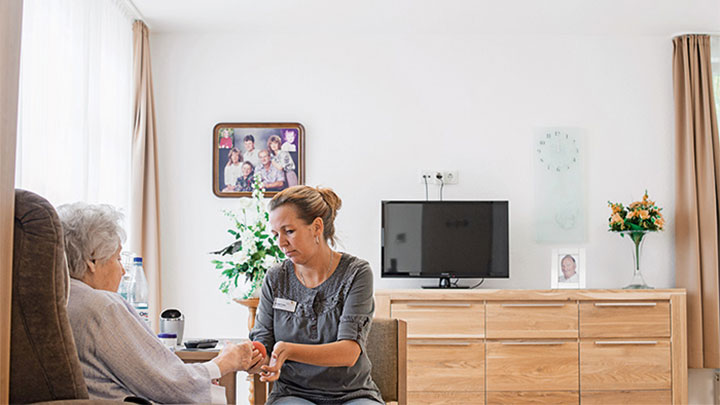 A staff taking care of a patient at Elderly Care Home under dynamic lighting by Philips Healtcare Lighting solutions
