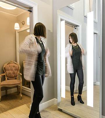 Woman checking her reflection in the AmbiScene Mirror created by Philips