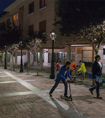 People are walking around on the Palencia streets at night lit by Philips lighting