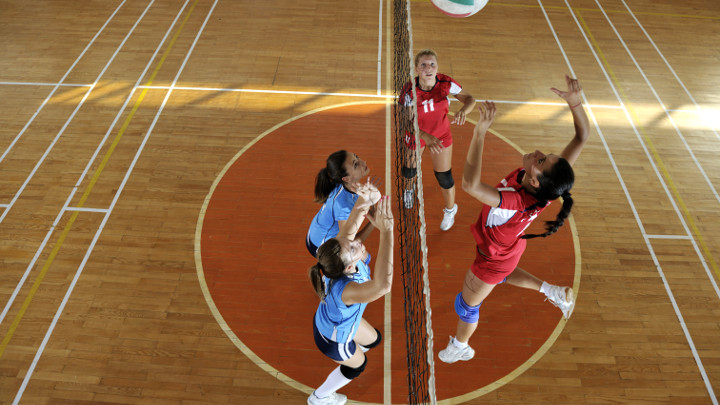 Female high school volleyball players jump to spike and block the ball during a match - educational institution